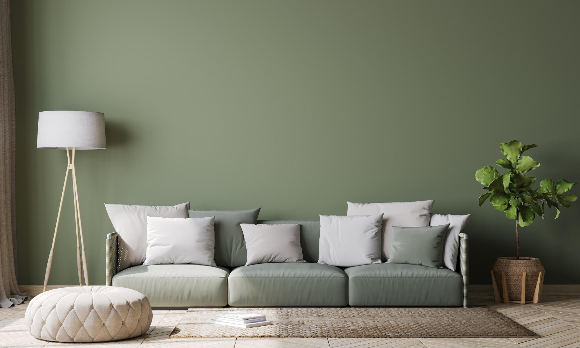 Modern living room with a green wall, green couch and white pillows